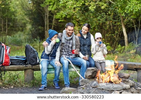 camping, travel, tourism, hike and people concept - happy family sitting on bench and drinking hot tea from cups at camp fire in woods - stock photo