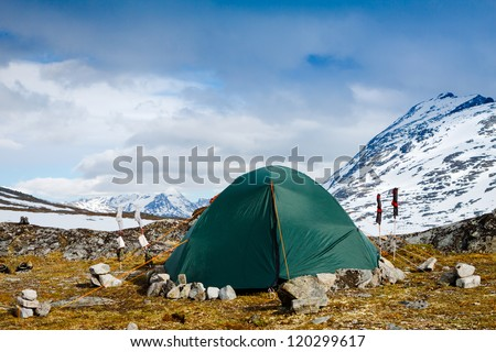 Camping with a tent in Alps with snow capped mountains - stock photo