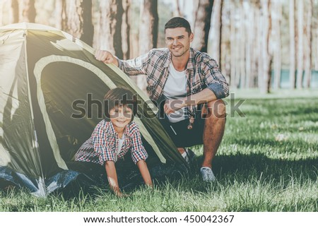 Camping with father. Cheerful father and son sitting near the tent while camping in the forest - stock photo