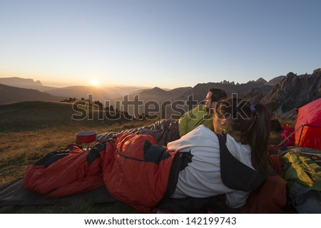 Camping with sleeping bag in the Dolomite - Sunset in base camp  - stock photo
