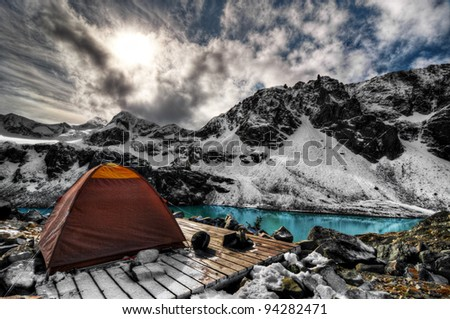 Campsite above turquoise mountain lake and snow capped mountains - stock photo