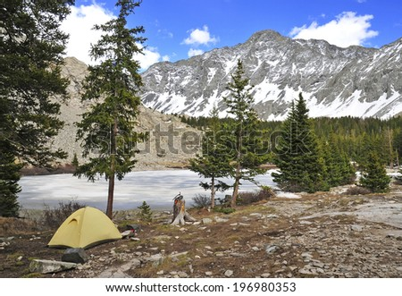 Campsite and Tent with Snow-capped peaks in the Mountains - stock photo