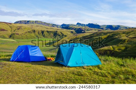 Campsite tents in Iceland - Summer camping with blue sky and mountains around. - stock photo