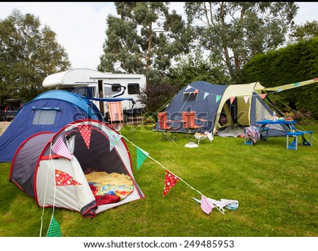 Campsite With Pitched Tents And Campervan  - stock photo