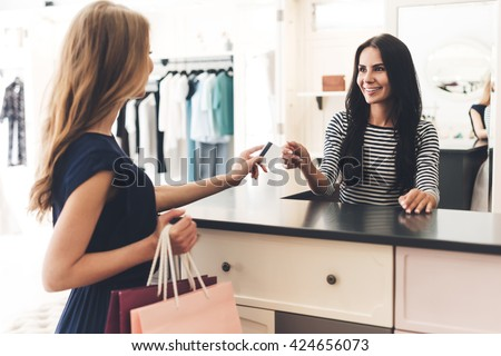 Can I pay with my card? Beautiful young woman with shopping bags giving her credit card to seller while standing at the clothing store - stock photo