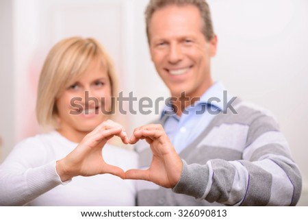 Can not live without you. Pleasant adult delighted couple forming heart and smiling while expressing love - stock photo