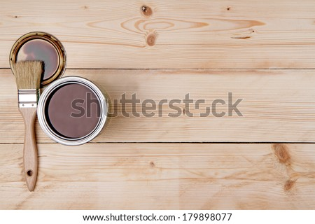 Can of paint and a paint brush on a wooden background - stock photo