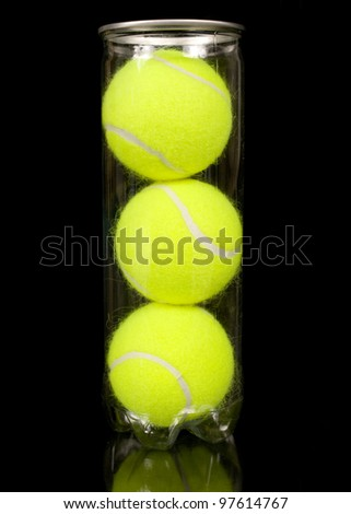 Can of three new tennis balls isolated on black background. - stock photo