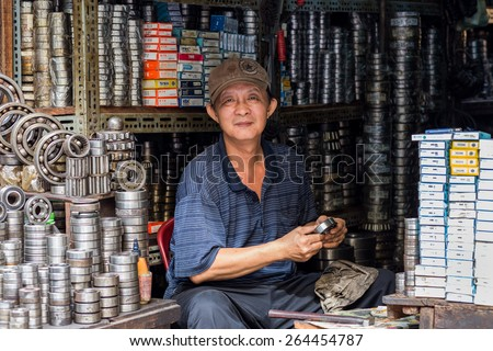 CAN THO, VIETNAM, DECEMBER 11, 2014: Portrait of A ball bearing seller cleaning a stuff in the Tan An market streets in Can Tho city, Vietnam. - stock photo