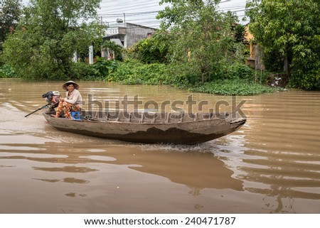 CAN THO, VIETNAM - JULY 29 2013: Vietnamese lady steers her boat down one of the rivers in the Mekong delta 20km south west of Can Tho  - stock photo