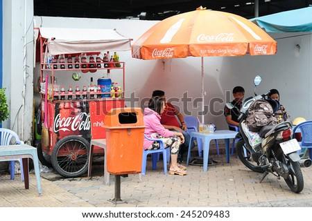 Can Tho, Vietnam. June 14, 2014 : Unidentified customers having a break at streets stall with Coca Cola push cart and umbrella at Can Tho, Vietnam on June 14, 2014. - stock photo