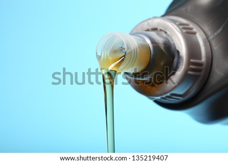 Can with car engine oil pouring in front  blue background - stock photo