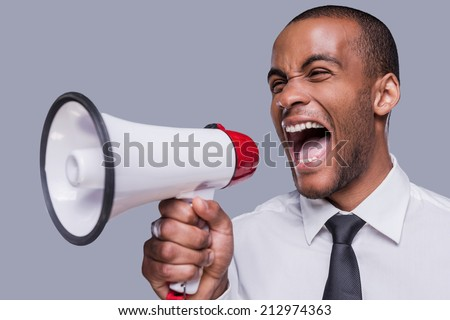 Can you hear me now? Furious young African man in formalwear shouting at megaphone while standing against grey background  - stock photo