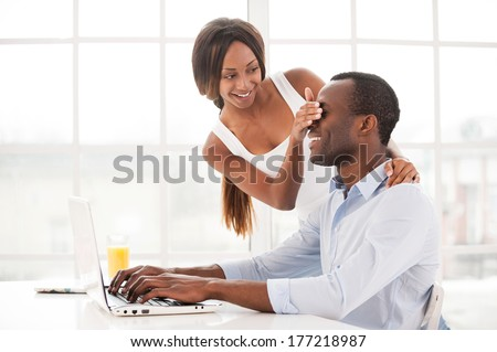 Can you stop working? Beautiful young African woman covering her boyfriend eyes while he is working at the laptop  - stock photo
