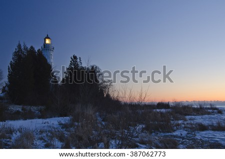 Cana Island Lighthouse shines into the pre-dawn light in Door County, Wisconsin.  The light turns off automatically just before sunrise each day. - stock photo