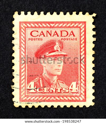 CANADA - CIRCA 1943: Red color postage stamp printed in Canada with portrait image of King George VI in military uniform. - stock photo