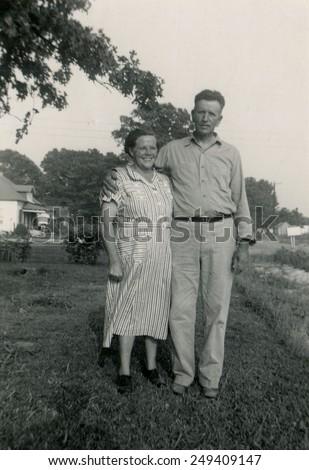 CANADA - CIRCA 1940s: Reproduction of an antique photo shows farmer's family posing in the garden near his home - stock photo