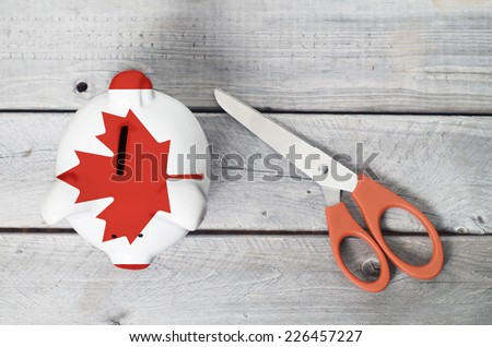 Canada cutting cost with a piggy bank overlaid by Canadian flag - stock photo