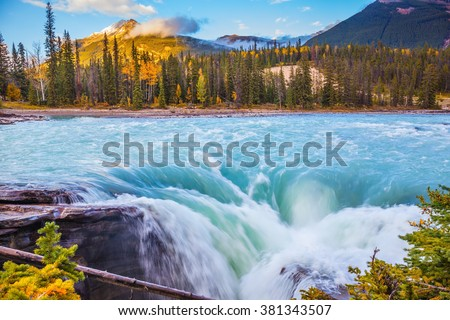 Canada, Jasper National Park. Powerful and scenic Athabasca Falls. Emerald water roars and foams on steep slope - stock photo