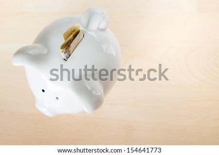 Canadian  $100 dollar bill, folded, sticking out of small white piggy bank on wooden cut board - stock photo