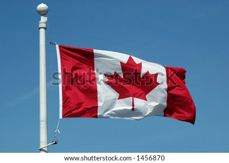 Canadian flag in blue sky background - stock photo
