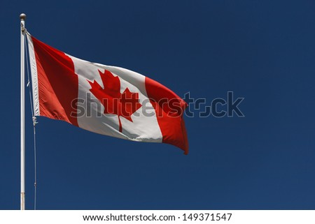 Canadian flag on pole with dark blue sky - stock photo