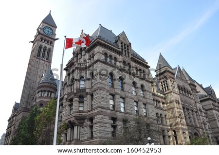 Canadian flag waving in front of Toronto's Old City Hall - stock photo
