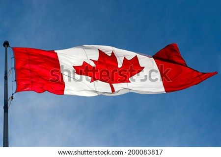 Canadian flag waving in the air over a beautiful blue sky, Canada Union Jack the national symbol of the union of all provinces in a federal country. - stock photo