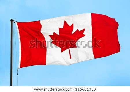 Canadian flag waving in the wind on a clear blue sky - stock photo