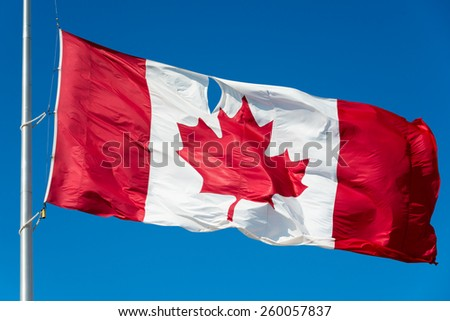 Canadian flag with a hole flies at half mast because of the killing of the first Canadian soldier in Iraq during the war against ISIS. - stock photo