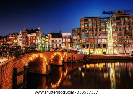 Canal in Amsterdam at night. Highlighting buildings and streets and is reflected in the water - stock photo