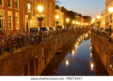 Canal in Utrecht, Netherlands. Houses, bicycles  and vintage street lamps along the canal at sunset. - stock photo