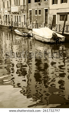 Canal in Venice. Boats and reflection of houses in the water. Aged photo. Sepia. - stock photo