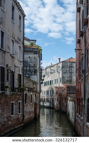 Canal  in Venice - old buildings, raw walls, closed shutters and doors near the water - stock photo