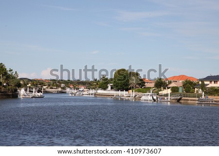 Canal on Bribie Island, Queensland, Australia, showing jetty, boats and houses - stock photo