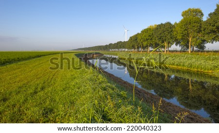 Canal through a rural landscape at sunrise - stock photo