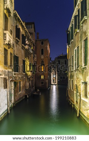 Canal with medieval palaces at night in Venice - stock photo