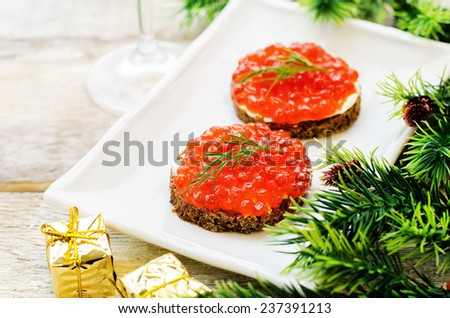 canape with red caviar and cream cheese on a white wood background. tinting. selective focus - stock photo