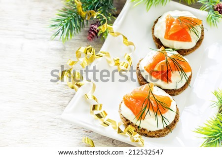 canape with salmon and cream cheese on a light background. tinting. selective focus on the  front canape - stock photo