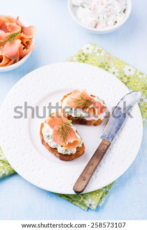 Canape with smoked salmon and cream cheese on plate, selective focus - stock photo