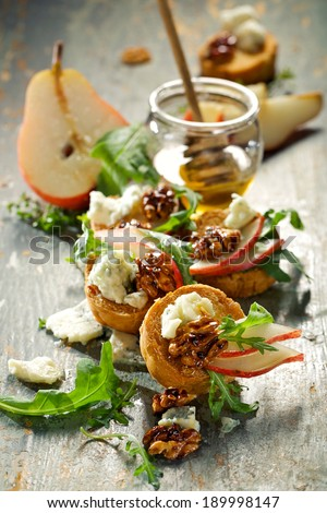 Canapes with blue cheese, fresh pear,  caramelized walnuts and arugula - stock photo