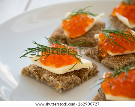 Canapes with red caviar and butter closeup - stock photo