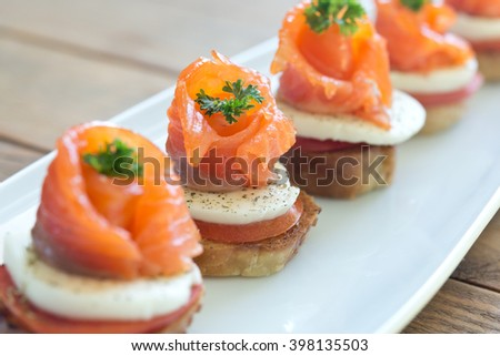 canapes with salmon and cheese on wooden table - stock photo