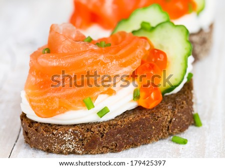 Canapes with salmon, red caviar, onion and cucumber   - stock photo