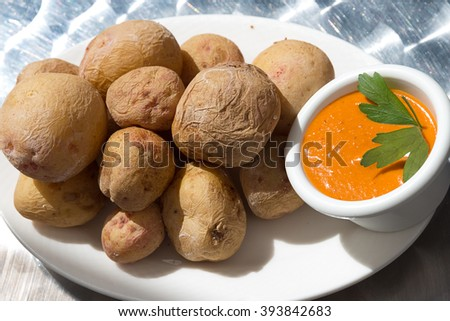 Canarian wrinkly potatoes - Papas Arrugadas and Mojo, Lanzarote. Small new potatoes which are cleaned with peel are usually served with a pepper sauce, called Mojo   - stock photo