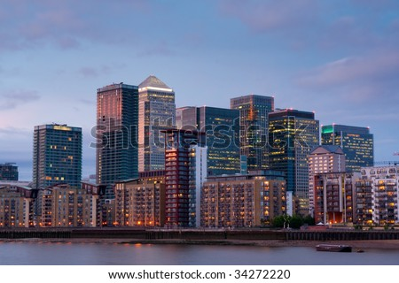 canary wharf, london's new financial district, by thames river at dusk, with scattered residential apartment block - stock photo