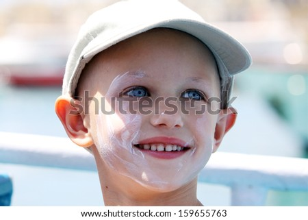 cancer child with sun cream on her face - stock photo