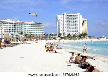CANCUN - JANUARY 22: Tourists enjoy the sunny weather and relaxing on the beautiful beach on 22 January 2015 in Cancun, Mexico. This is one of the best beaches in the Mexico. - stock photo