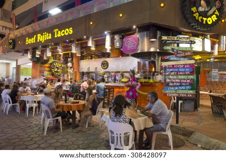 CANCUN, MEXICO - JULY 27, 2015: Tourists enjoy eating at the Taco Factory, a popular restaurant offering tasty Mexican food in Cancun's hotel zone - stock photo