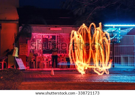 CANCUN, MEXICO - MARCH 26, 2011: Fire show at the local bar of the popular touristic resort. Night with illuminated street - stock photo